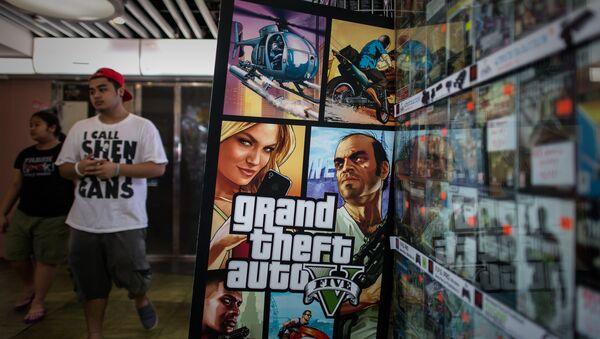 A man walks past a billboard of the Grand Theft Auto V video game in Hong Kong on September 17, 2013 - Sputnik International