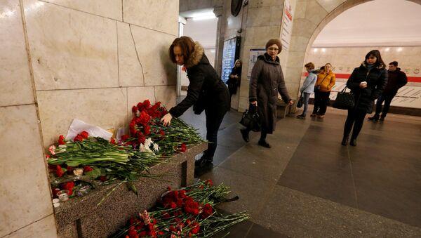 A woman lays flowers in memory of victims of a blast in St.Petersburg metro, at Tekhnologicheskiy institut metro station in St. Petersburg, Russia, April 4, 2017 - Sputnik International