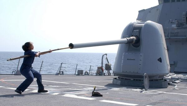 This picture released by tjeUS Navy shows Gunners Mate 2nd Class Shermel Howard cleaning the barrel of the MK-45, a 5-inch, 54-caliber gun system aboard USS Hopper (File) - Sputnik International