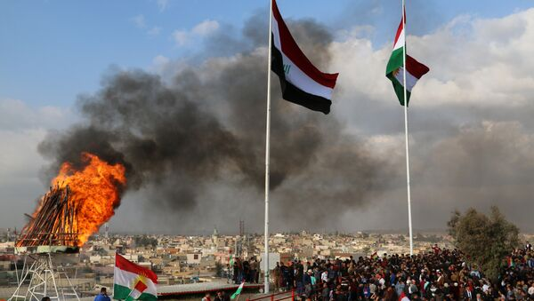 The Kurdish and Iraqi flag sway in the wind as a bonfire burns during the Noruz spring festival celebrations in the northern city of Kirkuk, about 240 kilometres (150 miles) north of Baghdad on March 20, 2017 - Sputnik International
