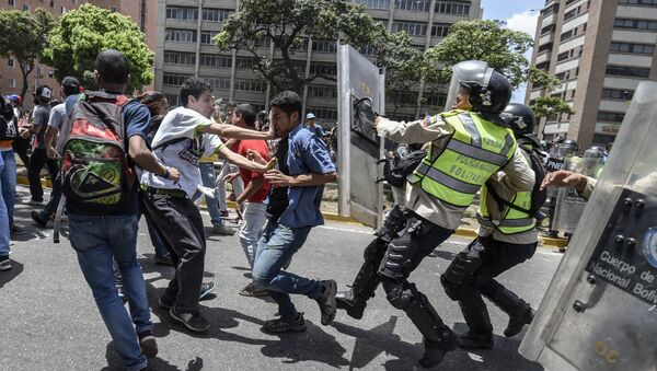 Venezuela's opposition activists clash with riot police agents during a protest against Nicolas Maduro's government in Caracas on April 4, 2017 - Sputnik International