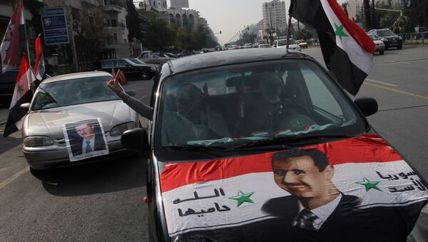 Syrians display national flags and banners with photos of Syrian President Bashar Assad during a pro-government event in Damascus, Syria. (File) - Sputnik International