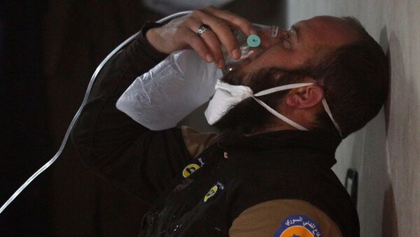 A civil defence member breathes through an oxygen mask, after what rescue workers described as a suspected gas attack in the town of Khan Sheikhoun in rebel-held Idlib, Syria April 4, 2017. - Sputnik International