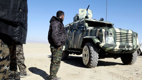 A fighter from the Syrian Democratic Forces, inspects a military vehicle supplied by the US-led coalition, as they gather near a village north-east of Raqa - Sputnik International