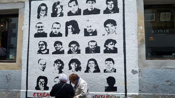 Women speak alongside a mural depicting imprisoned armed Basque group ETA members, under which reads We Want Them Home, in the Basque town of Hernani, Spain March 31, 2017. - Sputnik International