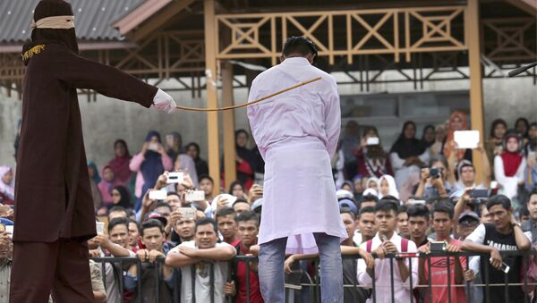In this Monday, March 20, 2017 photo, a Sharia law official whips a man convicted of adultery with a rattan cane in Banda Aceh, Indonesia. - Sputnik International
