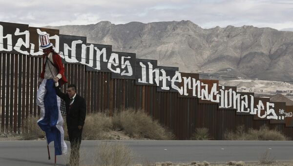 Protestors dressed as a diabolical Uncle Sam, on stilts, and Mexico's President Enrique Pena Nieto hold hands as they walk along the border fence in Ciudad Juarez, Mexico Sunday, Feb. 26, 2017. - Sputnik International
