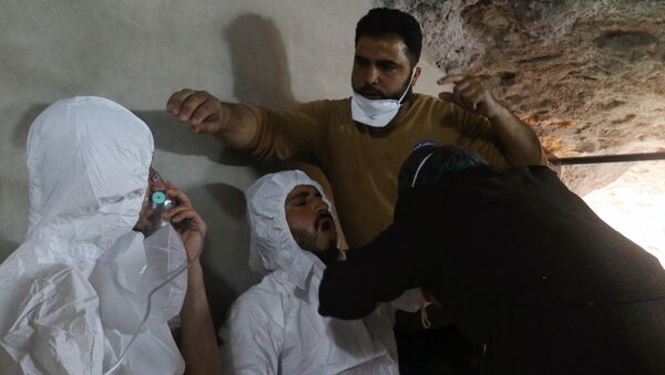 A man breathes through an oxygen mask as another one receives treatments, after what rescue workers described as a suspected gas attack in the town of Khan Sheikhoun in Idlib, Syria April 4, 2017 - Sputnik International