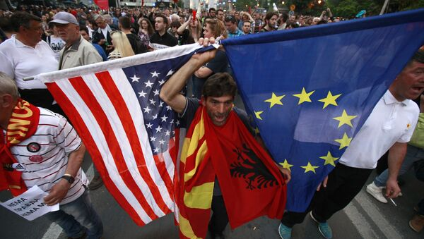 A protestor holds the flags of the United States, Macedonia, Albania and the European Union while attending a march through downtown Skopje, Macedonia, Monday, April 18, 2016 - Sputnik International
