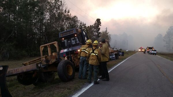 Firefighters and firefighting equipment arrive to deal with wildfire that quickly spread across acres of land, damaging many homes and forcing residents to evacuate in this image released on social media in Nassau County, Florida, U.S. on March 22, 2017 - Sputnik International