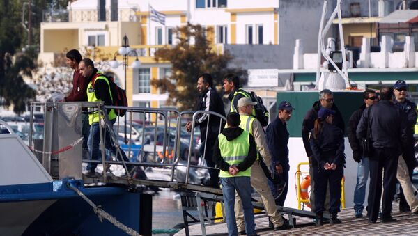 Frontex officials and Greek police escort migrants aboard a Turkish boat heading to Turkey from the port of Mytilene on the Greek island of Lesbos on October 21, 2016 - Sputnik International
