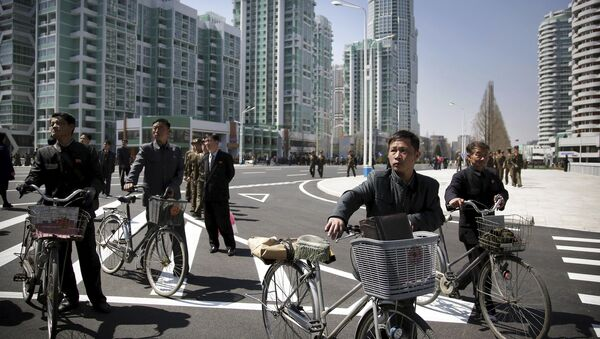 North Korean men push their bicycles along Ryomyong residential area, a collection of more than a dozen apartment buildings, on Thursday, April 13, 2017, in Pyongyang, North Korea. - Sputnik International