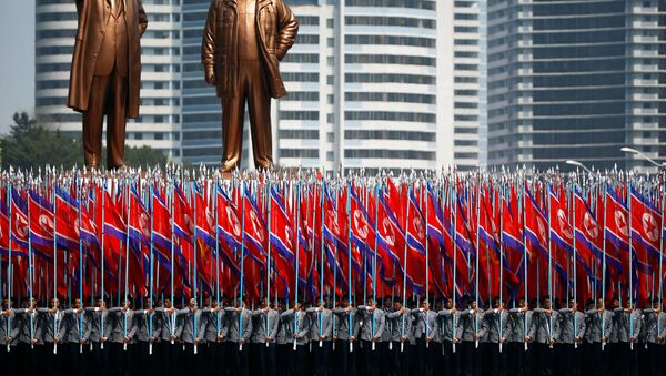 People carry flags in front of statues of North Korea founder Kim Il Sung (L) and late leader Kim Jong Il during a military parade marking the 105th birth anniversary Kim Il Sung, in Pyongyang April 15, 2017. - Sputnik International
