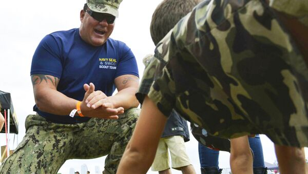 Chief Petty Officer Joseph Schmidt III, assigned to the Navy SEAL and SWCC Scout Team, encouraging a young fan to do pushups at the 2016 Stuart Air Show in Stuart, Fla. - Sputnik International