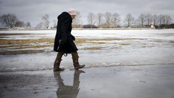An elderly woman walks on melted snow in Djurgaarden area in Stockholm on March 21, 2011 - Sputnik International