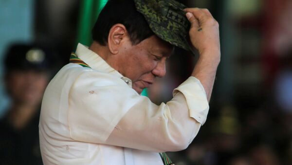 Philippine President Rodrigo Duterte tries on a military hat given to him during the 120th founding anniversary of the Philippine Army (PA) at Taguig city, metro Manila, Philippines April 4, 2017 - Sputnik International