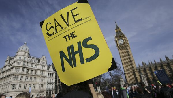 A protester holds a placard in support of the NHS in front of the Elizabeth Tower, also known as Big Ben at the Houses of Parliament during a march against private companies' involvement in the National Health Service (NHS) and social care services provision and against cuts to NHS funding in central London on March 4, 2017 - Sputnik International
