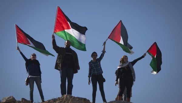 Palestinians wave national flags during a protest - Sputnik International