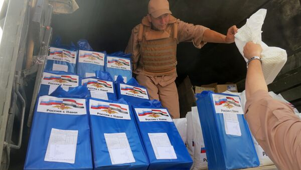(File) A picture taken during a press tour organized by the Russian Army shows a Russian soldier distributing food parcels on April 8, 2016 in al-Qaryatain, a town in the province of Homs in central Syria, a few days after Syrian regime forces seized it from jihadists of the Islamic State (IS) group - Sputnik International