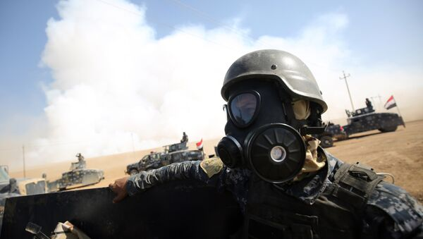 Iraqi forces wear gas masks for protection as smoke billows in the background after Islamic State (IS) group jihadists torched Mishraq sulphur factory, near the Qayyarah base, about 30 kilometres south of Mosul, during an operation to retake the main hub city from IS on October 22, 2016 - Sputnik International