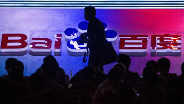 FILE - In this Sept. 2, 2011 file photo, a photographer walks past the logo of Baidu Inc., which operates China's dominant search engine, during a technology innovation conference held by the company at China's National Convention Center in Beijing, China. China issued new regulations on Saturday, June 25, 2016 demanding search engines clearly identify paid search results, months after a terminally-ill cancer patient complained that he was misled by the giant search engine Baidu. - Sputnik International