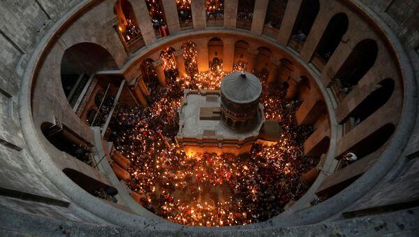 Верующие со свечами во время сошествия благодатного огня в Храм Гроба Господня в Иерусалиме - Sputnik International
