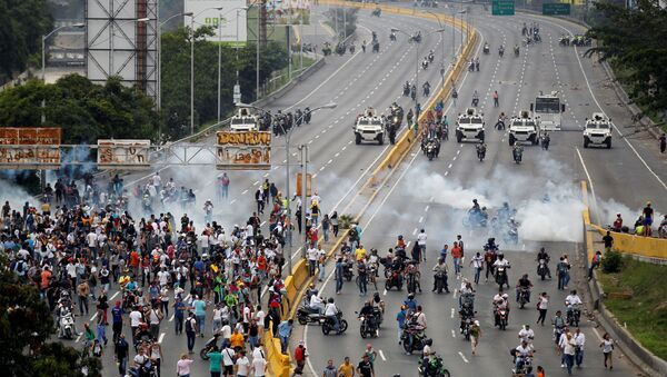 Demonstrators run away from tear gas during clashes with police while rallying against Venezuela's President Nicolas Maduro in Caracas, Venezuela, April 20, 2017. - Sputnik International