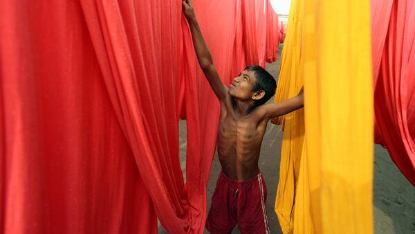 In this Saturday, Dec. 22, 2012 file photo, a Bangladeshi child works at a clothes-dyeing factory in Narayanganj, outskirts of Dhaka, Bangladesh. - Sputnik International