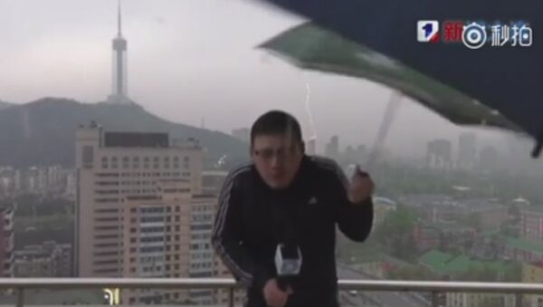 Chinese weather man hit by lightning bolt while holding an umbrella doing LIVE broadcast in a storm - Sputnik International