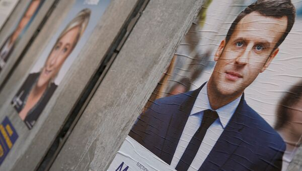 People walk past campaign posters of Emmanuel Macron (L), head of the political movement En Marche! (Onwards!), and Marine Le Pen (R), French National Front (FN) political party leader, two of the eleven candidates who run in the 2017 French presidential election, are seen in Paris, France, April 10, 2017 - Sputnik International