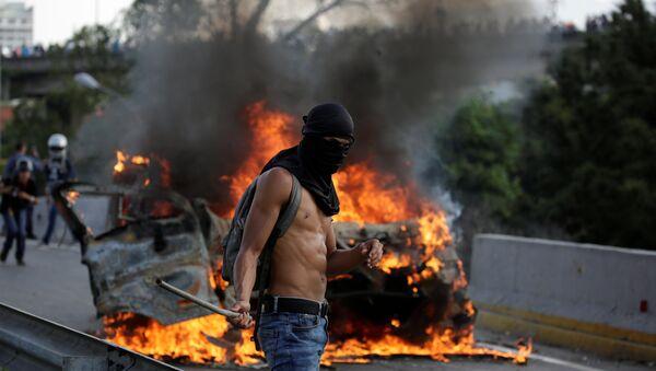 A demonstrator stands near fire during a rally against Venezuela's President Nicolas Maduro in Caracas, Venezuela April 24, 2017 - Sputnik International