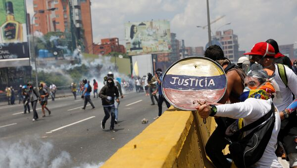 Opposition supporters use a shield reading Justice as they clash with security forces during a rally against Venezuela's President Nicolas Maduro in Caracas, Venezuela April 26, 2017 - Sputnik International
