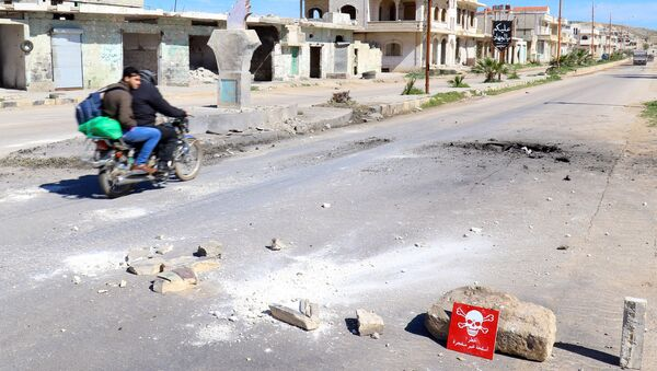 Men ride a motorbike past a hazard sign at a site hit by an airstrike on Tuesday in the town of Khan Sheikhoun in rebel-held Idlib, Syria April 5, 2017 - Sputnik International