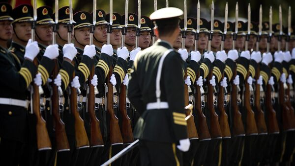 A Chinese People's Liberation Army soldier watches the position of members of a guard of honor as they prepare for a welcome ceremony for visiting Indian Prime Minister Manmohan Singh, outside the Great Hall of the People in Beijing Wednesday, Oct. 23, 2013. - Sputnik International