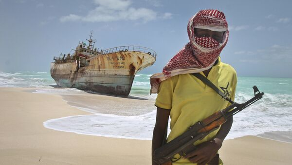 In this Sunday, Sept. 23, 2012 file photo, masked Somali pirate Hassan stands near a Taiwanese fishing vessel that washed up on shore after the pirates were paid a ransom and released the crew, in the once-bustling pirate den of Hobyo, Somalia. - Sputnik International