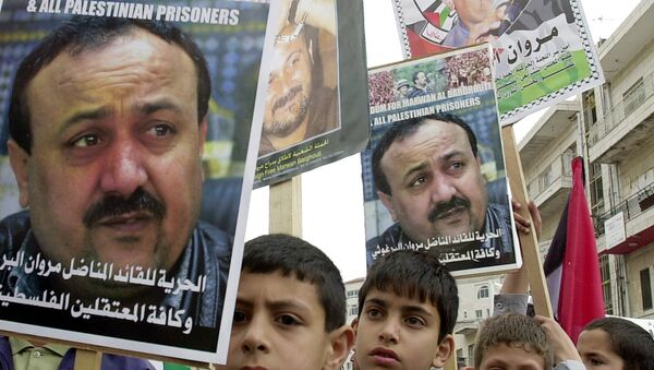 Palestinian youths hold pictures of Palestinian uprising leader Marwan Barghouti, detained in Israel, during a prisoners rally in the West Bank town of Ramallah Tuesday, April 15, 2003. - Sputnik International