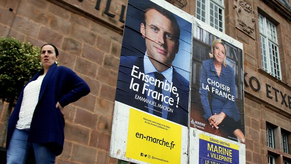 A woman walks near election campaign posters for French centrist presidential candidate Emmanuel Macron, left, and far-right candidate Marine Le Pen, in Saint Jean Pied de Port, southwestern France, Friday May 5, 2017 - Sputnik International