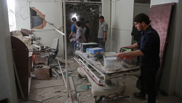 Syrians salvage medical items from a hospital following an air strike a rebel-controlled town in the eastern Ghouta region on the outskirts of the capital Damascus on May 1, 2017 - Sputnik International