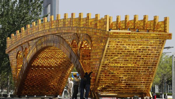 Workers install wires on a 'Golden Bridge of Silk Road' structure on a platform outside the National Convention Center, the venue which will hold the Belt and Road Forum for International Cooperation, in Beijing - Sputnik International