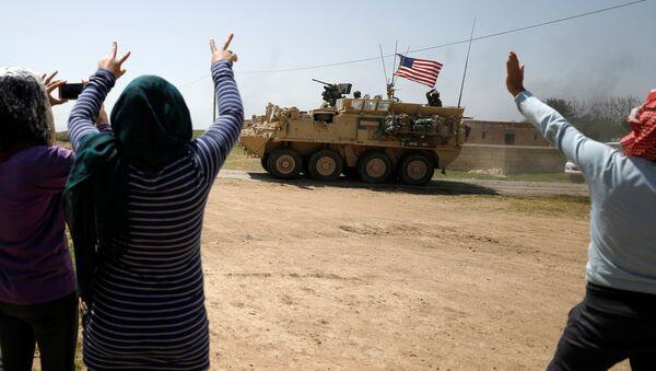 People gesture at a US military vehicle travelling in Amuda province, northern Syria April 29, 2017. - Sputnik International