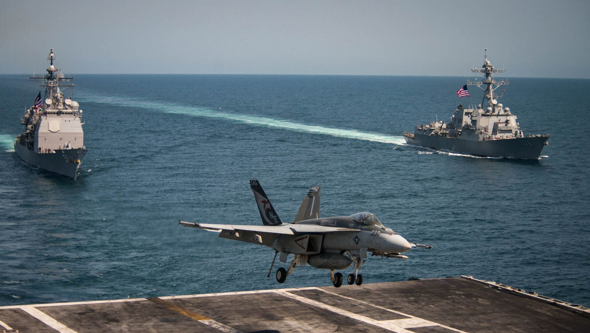 An F/A-18E Super Hornet lands on the flight deck of the U.S. Navy aircraft carrier USS Carl Vinson as the Ticonderoga-class guided-missile cruiser USS Lake Champlain (L) and the Arleigh Burke-class guided-missile destroyer USS Wayne E. Meyer transit the western Pacific Ocean May 3, 2017. - Sputnik International, 1920, 04.08.2021