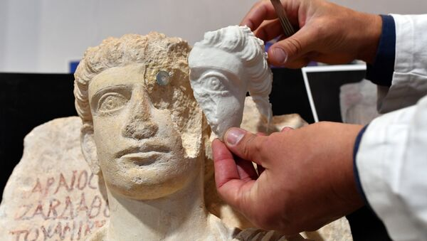 A restorer fixes a restored piece of the face of a man bust, which is one of the two funeral reliefs from Palmyra archeological site that will be restored at the Higher Institute of Conservation and Restoration (ISCR - Istituto Superiore per la Conservazione ed il Restauro) in Rome, on February 16, 2017. - Sputnik International