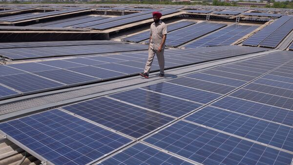 An Indian security personnel poses for media as he walks over rooftops covered in solar panels at the Solar Photovoltaic Power Plant, some 45kms from Amritsar. (File) - Sputnik International