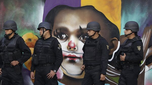 In this Monday, Jan. 9, 2017 photo, police providing security walk past street art as thousands march against the government of Enrique Pena Nieto following a 20 percent rise in gas prices in Mexico City. - Sputnik International