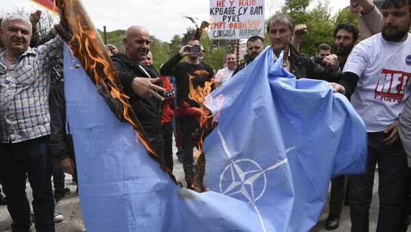 Anti-NATO demonstrators burn a NATO flag in front of a a banner that reads: No to NATO, your hands are bloody - Death to fascism, freedom to the people, during a protest outside the hall before the parliament session in Cetinje, Montenegro, Friday, April 28, 2017 - Sputnik International