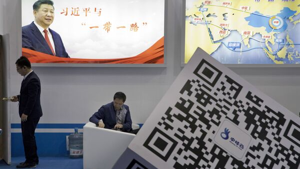 Visitors at a technology conference wait near illuminated boards highlighting Chinese President Xi Jinping's signature One Belt, One Road foreign policy plan in Beijing, China, Friday, April 28, 2017 - Sputnik International