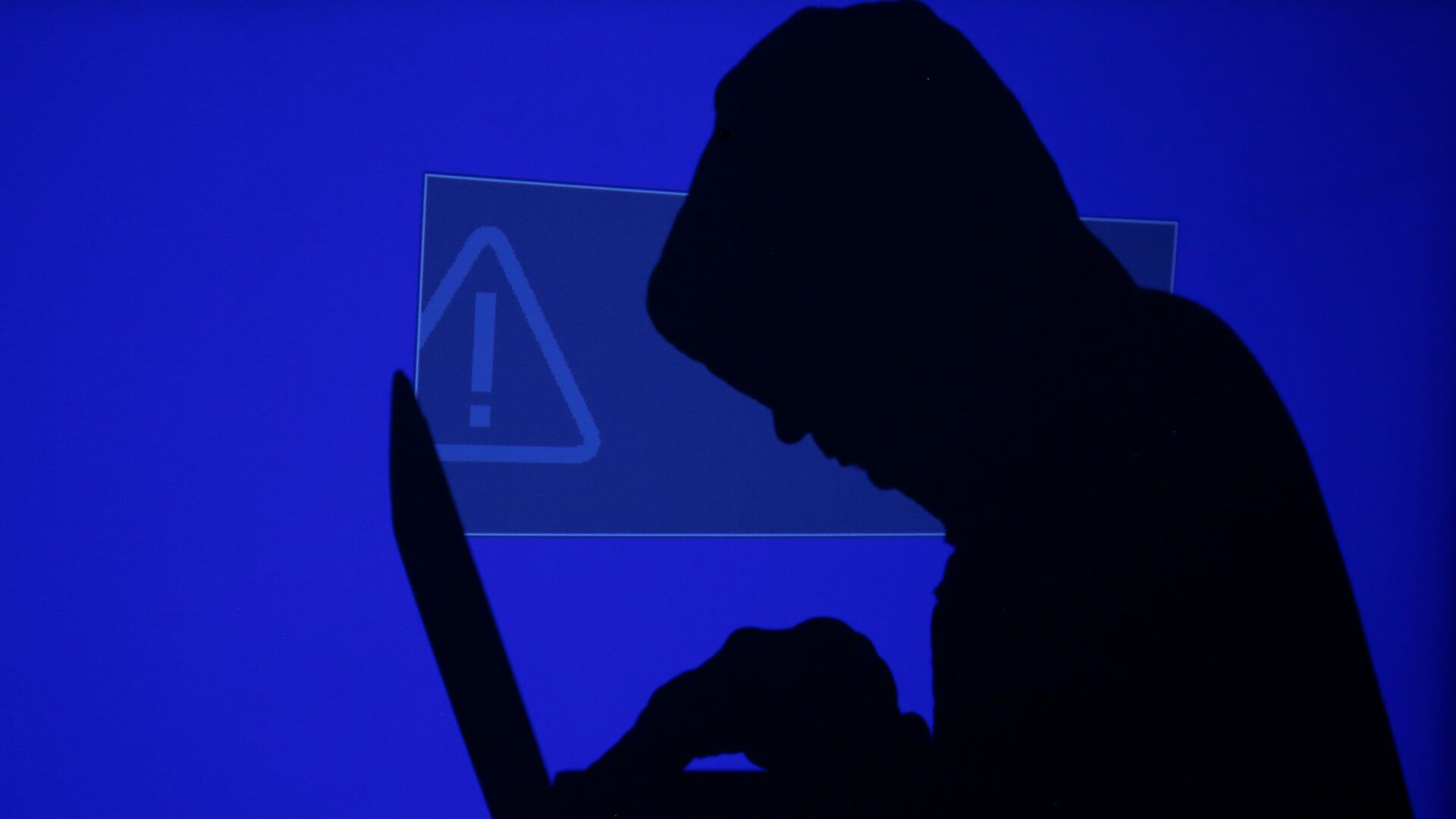 A hooded man holds a laptop computer as blue screen with an exclamation mark is projected on him in this illustration picture taken on May 13, 2017 - Sputnik International, 1920, 16.09.2021