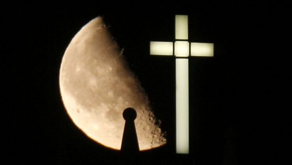 A third quarter Buck Moon rises behind a spire on the top of the bell tower next to a lighted cross - Sputnik International