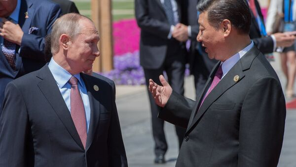 May 15, 2017. Russian President Vladimir Putin and Chinese President Xi Jinping, right, during a group photo session for the participants in a roundtable summit held as part of the Belt and Road Forum, in front of the Yanqi Lake International Convention Center. - Sputnik International