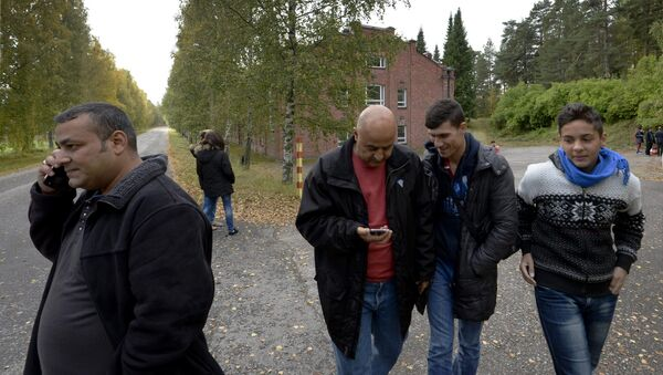 In this photo taken Friday, Sept. 25, 2015, Iraqi asylum seekers stand outside a refugee center located in the former army barracks, Lahti, Finland. Finland - Sputnik International